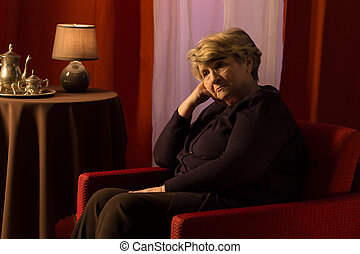Thoughtful sad woman sitting in vintage style room