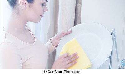 Young woman cleaning plate - Dusting china. Young beautiful...