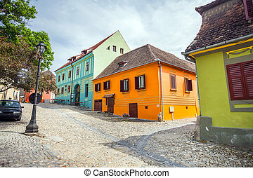 Stone paved old streets with colored houses from Sighisoara