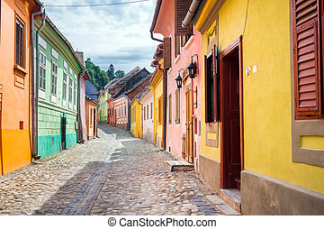 Stone paved old streets with colored houses from Sighisoara...