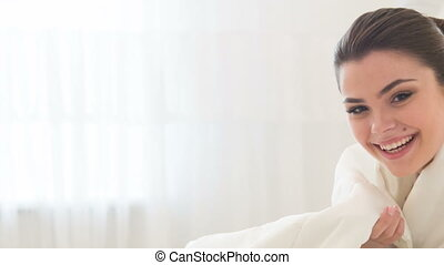 Young smiling woman sitting on bed - I am so shy. Young...