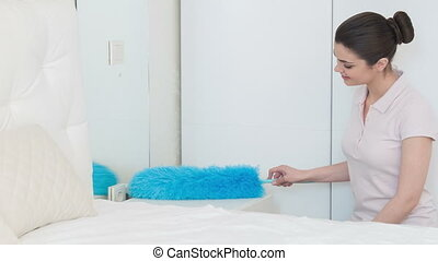 Young woman dusting her bedroom - Everything will be clean....