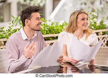 Romantic date - Beautiful young couple reading menu at...