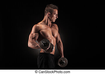 Muscular man with dumbbells on black background - Handsome...