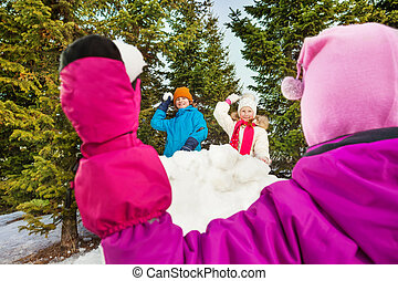 Girl throwing snowball from the back to throw - Girl...