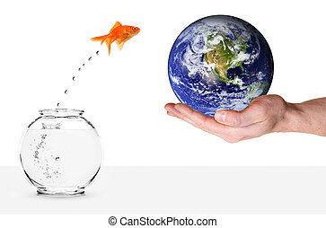 goldfish jumping out of fishbowl and into planet earth held...