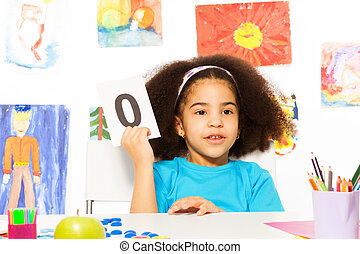 African girl holds flashcard with zero at desk - African...