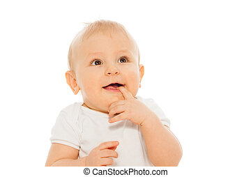 Portrait of happy baby with finger in his mouth wearing...