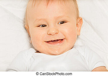 Happy face of small baby wearing white bodysuit