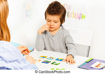 Concentrated boy plays developing game at table -...