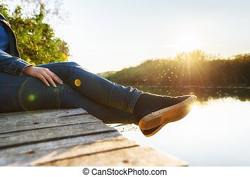 Woman relaxing on jetty at evening hours