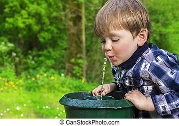 cute child drinking from a fountain - cute little boy...
