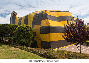 House is covered by tent for fumigation - Brown and yellow...