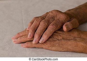 folded elders hands - elderly hands folded over white...