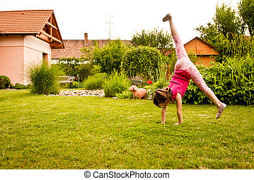 Child doing cartwheel in backyard - Small child girl doing...