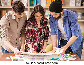 Designers - Three young creative designers working on...