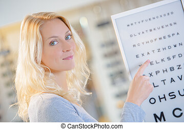 Lady pointing at eye test chart