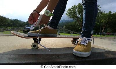 skateboarder hands tying shoelace on skateboard