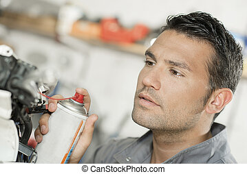 Mechanic using lubrication spray