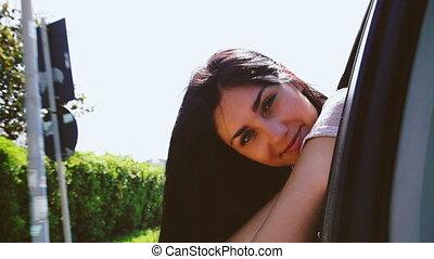 woman looking camera from car - Cute young woman having fun...