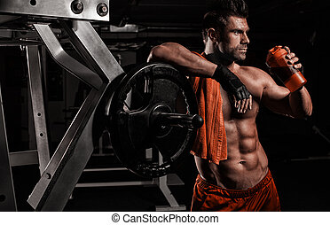 the very muscular sporty guy drinking protein in dark weight...