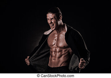 Portrait of screaming bodybuilder with tight muscles and his...