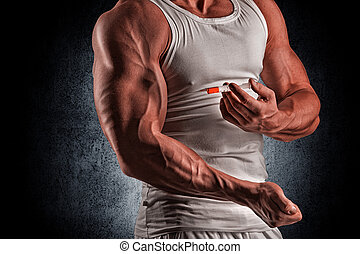 a muscular man with a syringe - muscular man doing a shot in...