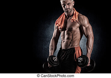 Muscular bodybuilder guy doing exercises with dumbbells over...