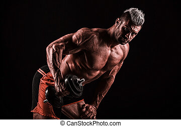athletic young caucasian man in studio on black background...