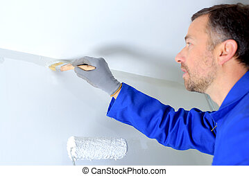 Decorator painting a wall