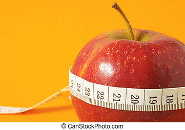 Diet Apple - Measuring Tape Wrapped Around a Red Apple as a...