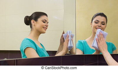 Young woman cleaning mirror - From different angles Pretty...