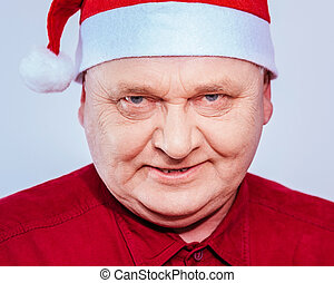 Spiteful man in Santa Claus hat - Close up portrait of evil...