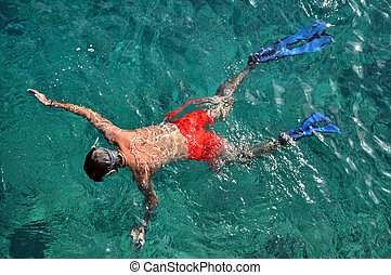 Man with mask snorkeling and in clear water