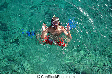 Man with mask snorkeling and doing ok sign