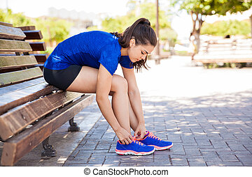 Tying tennis shoes in a park - Profile view of a young woman...