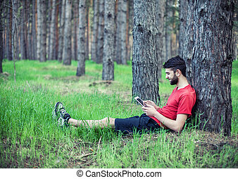Boy under a tree - The boy sits under a tree and reads the...