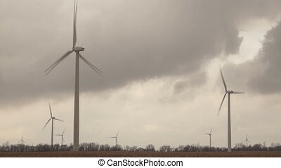 Three Wind Turbines Spin on Farm Land under Developing Storm...