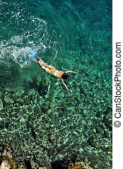 Woman snorkeling in clear sea water