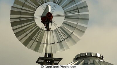 Windmill Spins Fast Above Farm Silo Pumping Water - Farm...