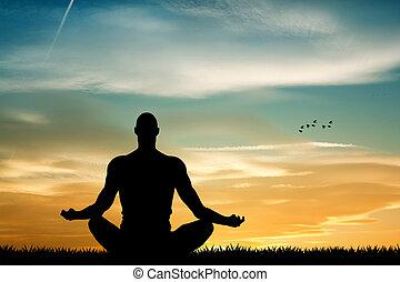 Man in meditation at sunset