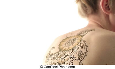 View of womans back with beautiful henna pattern - View of...