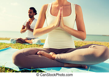 close up of couple making yoga exercises outdoors - fitness,...