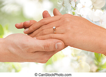 close up of man and woman hands with wedding ring - jewelry,...