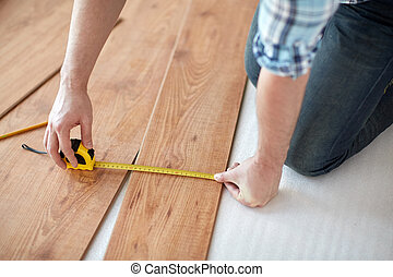 close up of male hands measuring flooring - repair,...
