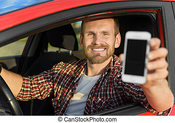 Man in car driving showing smart phone - Man in car driving...