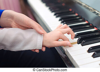 Woman teaching little girl to play the piano.