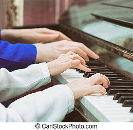 Woman teaching little girl to play the piano