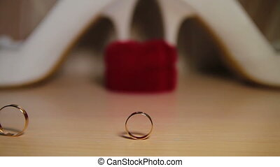 Two Wedding Rings Rolling On The Table - This is a shot of...
