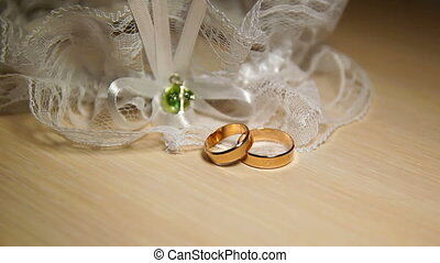Two Wedding Rings With Lace On The Table
